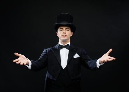 lazo negro: magia, performance, circo, espect�culo concepto - mago con sombrero de copa mostrando truco Foto de archivo