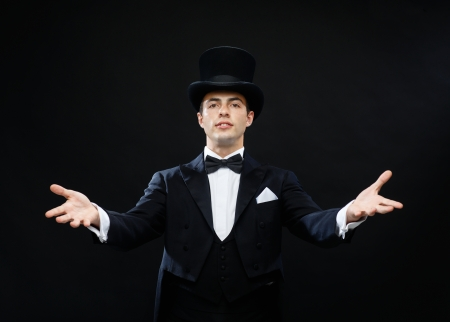 conjuring: magic, performance, circus, show concept - magician in top hat showing trick
