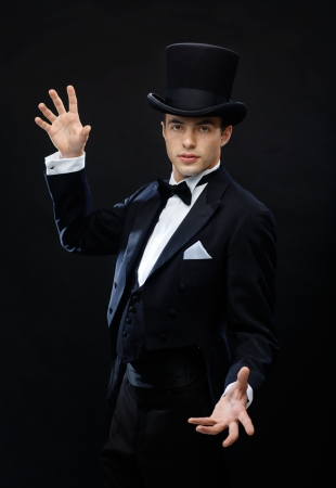 magic, performance, circus, show concept - magician in top hat showing trick Imagens - 23671536