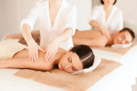 relaxation massage: health and beauty, resort and relaxation concept - couple in spa salon getting massage Stock Photo