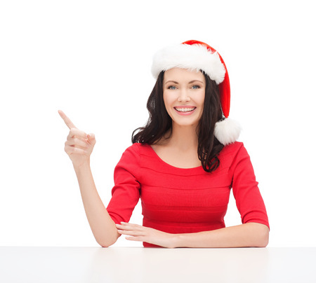 christmas, x-mas, winter, happiness concept - smiling woman in santa helper hat pointing to something Stock Photo - 23671510
