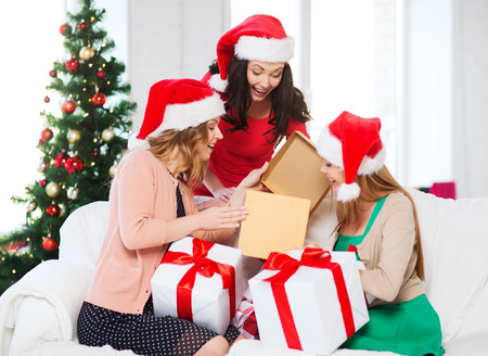 three presents: christmas, x-mas, winter, happiness concept - three smiling women in santa helper hats with many gift boxes Stock Photo