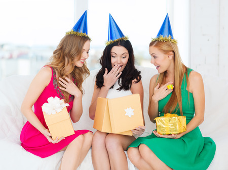 fancy box: celebration, friends, bachelorette party, birthday concept - three smiling women wearing blue hats with gift boxes