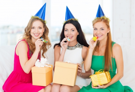 celebration, friends, bachelorette party, birthday concept - three smiling women wearing blue hats with gift boxes blowing favor horns photo
