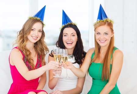 birthday champagne: celebration, drinks, friends, bachelorette party, birthday concept - three smiling women wearing blue hats with champagne glasses