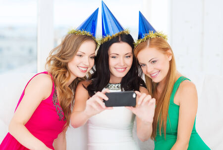 celebration, friends, bachelorette party, birthday concept - three smiling women in blue hats having fun with smartphone photo camera photo