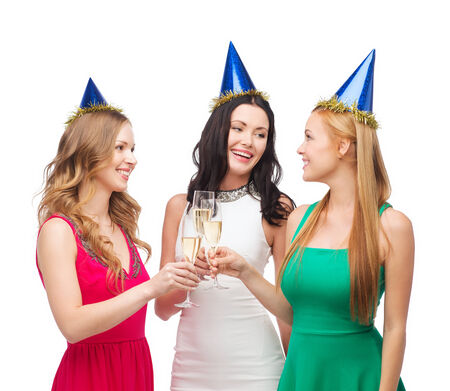 bachelorette party: celebration, drinks, friends, bachelorette party, birthday concept - three smiling women wearing blue hats with champagne glasses