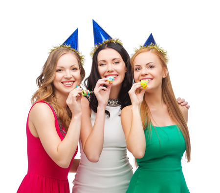 favor: celebration, friends, bachelorette party, birthday concept - three smiling women wearing blue hats and blowing favor horns