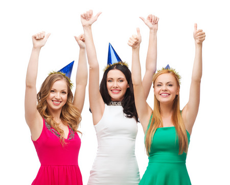celebration, friends, bachelorette party, birthday concept - three smiling women wearing blue hats and showing thumbs up photo