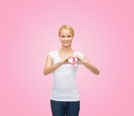 healthcare, medicine and breast cancer concept - woman in blank t-shirt with pink cancer ribbon photo