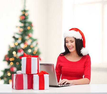 christmas, x-mas, online shopping concept - woman in santa helper hat with gift boxes and laptop computer photo