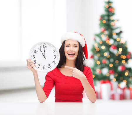 christmas, x-mas, winter, happiness concept - smiling woman in santa helper hat with clock showing 12 Stock Photo - 23671506