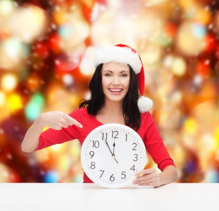 christmas, x-mas, winter, happiness concept - smiling woman in santa helper hat with clock showing 12 Stock Photo - 23682367