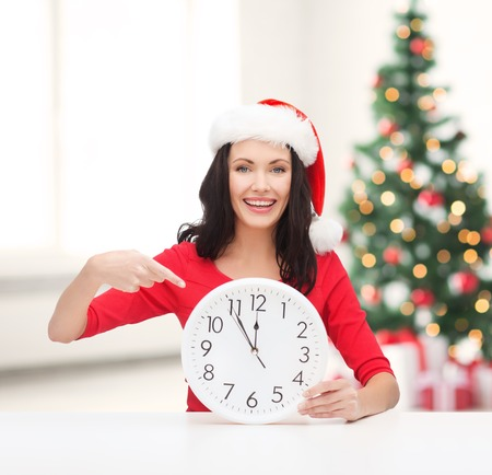 christmas, x-mas, winter, happiness concept - smiling woman in santa helper hat with clock showing 12 Stock Photo - 23671466