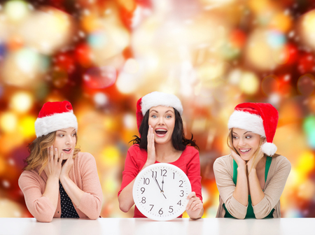 christmas, x-mas, winter, happiness concept - three smiling women in santa helper hats with clock showing 12 Stock Photo - 23682371