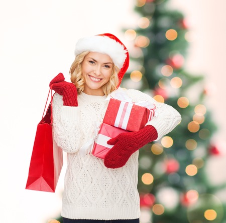 shopping, sale, gifts, christmas, x-mas concept - smiling woman in santa helper hat with shopping bags and gift boxes photo