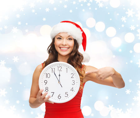 christmas, x-mas, winter, happiness concept - smiling woman in santa helper hat with clock showing 12 Stock Photo - 23671452