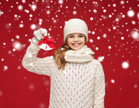 christmas, x-mas, winter, happiness concept - smiling girl in hat, muffler and gloves with jingle bells Stock Photo
