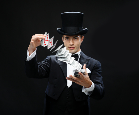 magic, performance, circus, gambling, casino, poker, show concept - magician in top hat showing trick with playing cards Stock Photo