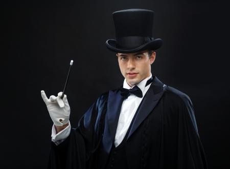 mago: performance, circo, espectáculo concepto - mago con sombrero de copa con la varita mágica mostrando truco