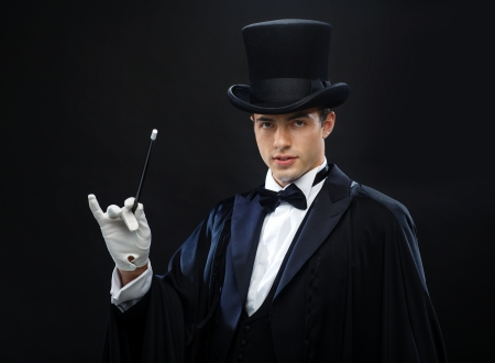 magic trick: performance, circus, show concept - magician in top hat with magic wand showing trick