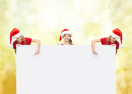 christmas, x-mas, people, advertisement, sale concept - happy children in santa helper hats with blank white board photo