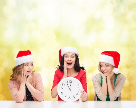 christmas, x-mas, winter, happiness concept - three smiling women in santa helper hats with clock showing 12 Stock Photo - 23671398