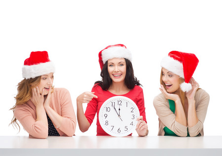 christmas, x-mas, winter, happiness concept - three smiling women in santa helper hats with clock showing 12 Stock Photo - 23671352