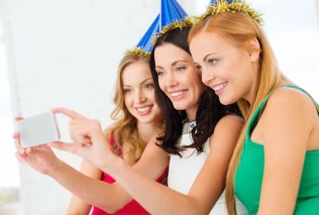 despedida de soltera: celebración, amigos, despedida de soltera, cumpleaños concepto - tres mujeres sonrientes en sombreros azules que se divierte con la cámara de fotos del smartphone