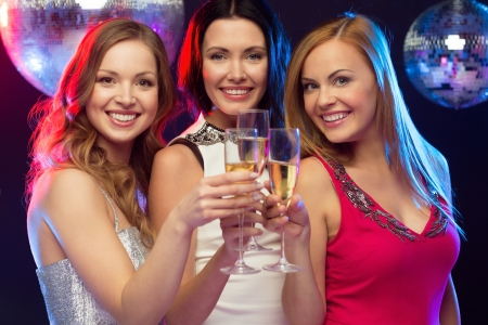 out: new year, celebration, friends, bachelorette party, birthday concept - three beautiful woman in evening dresses with champagne glasses Stock Photo
