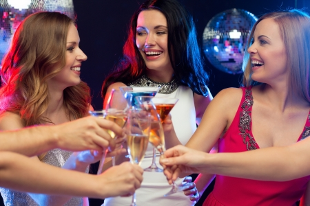 new year, celebration, friends, bachelorette party, birthday concept - three women in evening dresses with cocktails in club or bar photo