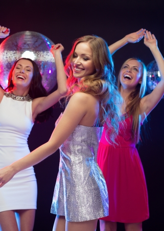 bachelorette: party, new year, celebration, friends, bachelorette party, birthday concept - three beautiful woman in evening dresses dancing in the club