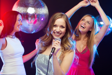 party, new year, celebration, friends, bachelorette party, birthday concept - three women in evening dresses dancing and singing karaoke photo