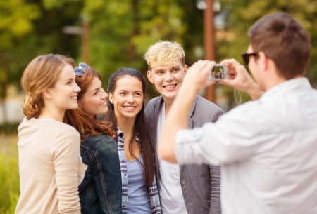 summer holidays and teenage concept - group of teenagers taking photo outside photo