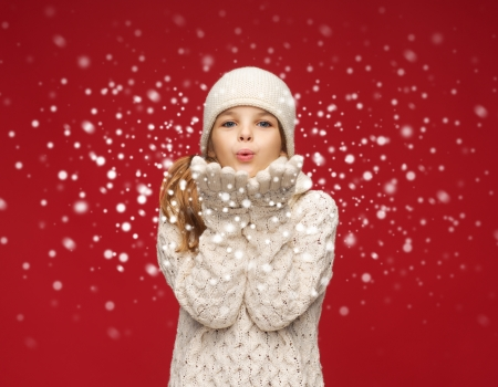 christmas, x-mas, people, happiness concept - happy girl in winter clothes blowing on palms Stock Photo
