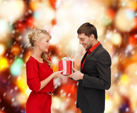 christmas, x-mas, winter, valentines day, birthday, happiness, couple concept - smiling woman and man with gift box photo