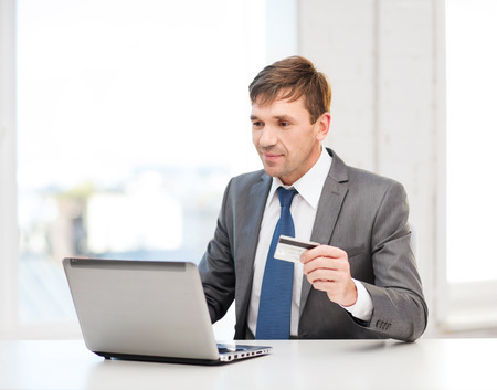 business, online banking, internet shopping concept - smiling man with laptop and credit card in office Stock Photo