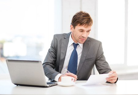 technology, business and office concept - handsome businessman working with laptop computer and documents photo