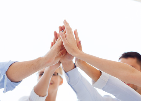 five: success and winning concept - happy business team giving high five in office