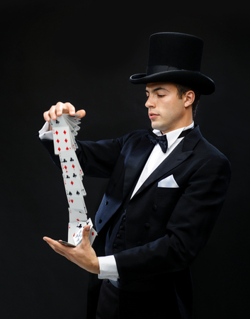 circus performers: magic, performance, circus, gambling, casino, poker, show concept - magician in top hat showing trick with playing cards Stock Photo