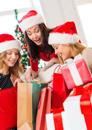 shopping, sale, gifts, christmas, x-mas concept - smiling women in santa helper hats with shopping bags and many gift boxes photo
