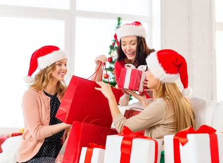 exchanging: shopping, sale, gifts, christmas, x-mas concept - smiling women in santa helper hats with shopping bags and many gift boxes