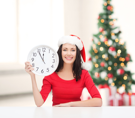 christmas, x-mas, winter, happiness concept - smiling woman in santa helper hat with clock showing 12 Stock Photo - 23682567