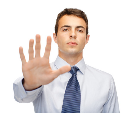 veto: business and office, ban, veto, warning concept - attractive buisnessman making stop gesture