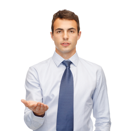 business and office, advertising, people concept - friendly young buisnessman showing something on the palm of his hand photo