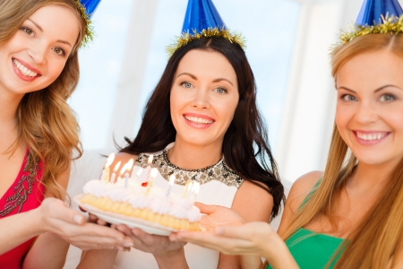 celebration, food, friends, bachelorette party, birthday concept - three smiling women wearing blue hats holding cake with candles photo