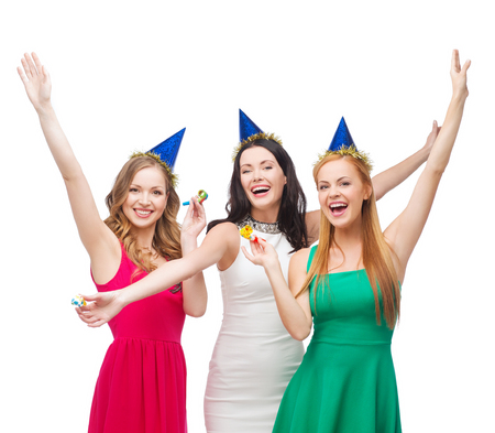 celebration, friends, bachelorette party, birthday concept - three smiling women wearing blue hats and blowing favor horns and waving hands photo