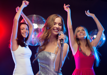 """cantando: partido, """"año nuevo"""", celebración, amigos, despedida de soltera, cumpleaños concepto - tres mujeres en vestidos de noche bailando y cantando karaoke Foto de archivo"""