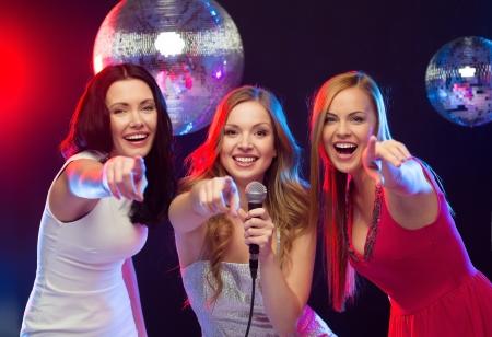 """partij, """"nieuwe jaar"""", viering, vrienden, vrijgezellenfeest, verjaardag concept - drie vrouwen in avondjurken dansen en zingen karaoke"""