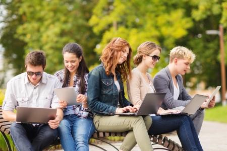夏、インターネット、教育、キャンパス、10 代のコンセプト - 学生または出かけるラップトップおよびタブレット コンピューターと 10 代の若者のグ